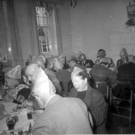 Photo:Men and women enjoy Christmas dinner in one of the House Blick day rooms, c. 1962