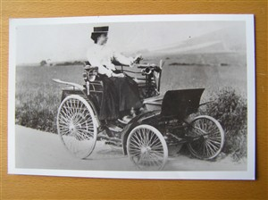 Photo:Winifred Turner seated upon an early model Benz