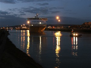Photo:Led by the pilot boat, Cote d'Albatre heads down river.