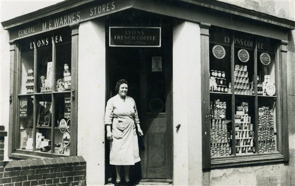 Photo:Mrs Warnes outside 'M.E. Warnes General Stores', 1 High Street. Telephone: Newhaven 299. Early 1950s