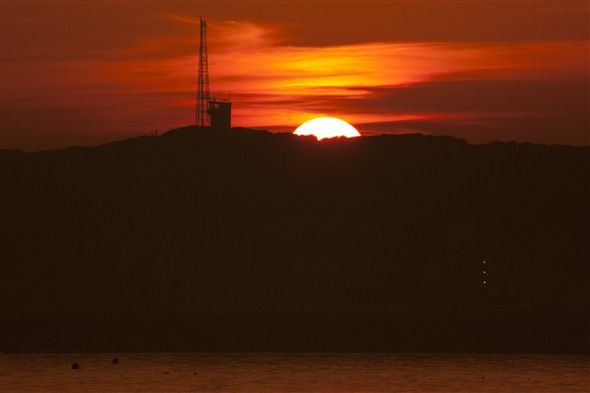 Photo:The sun dips down behind Castle Hill
