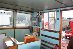 Photo:The aft starboard corner of the wheelhouse, with all the original light switches from 1960! Almost all the varnished woodwork is original, like the signal flag locker at the left of the photo.
